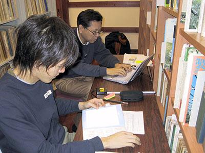 学生と資料整理を行う筆者