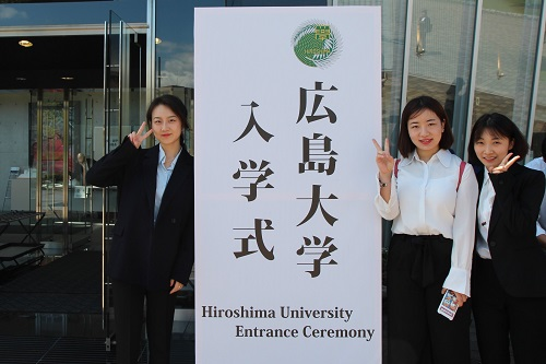 New students taking commemorative photos in front of the sign board