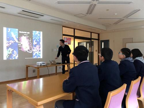 青井准教授から研究について説明を受けています。