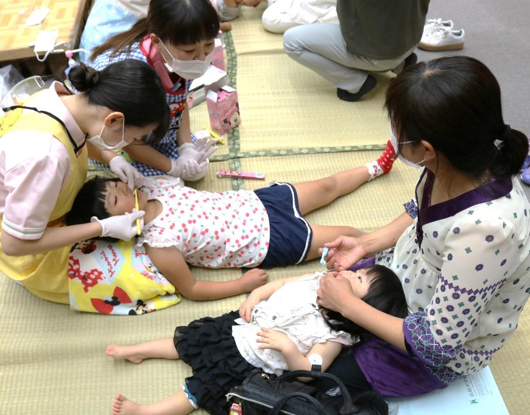 姉妹仲良く仕上げ歯みがき指導を受ける親子連れ