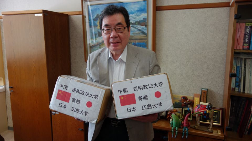 西南政法大学から寄贈されたマスクの箱を手にする江頭プログラム長