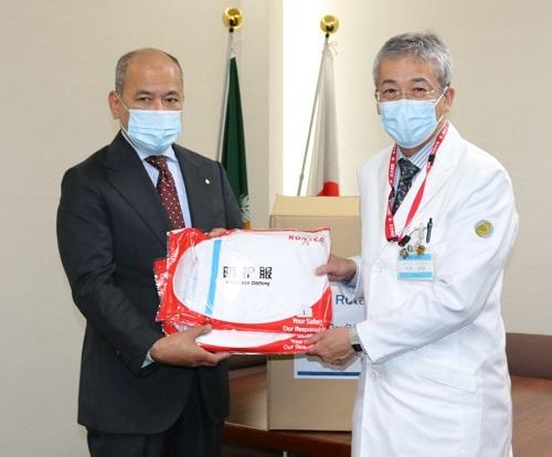 木内病院長(右)に防護服を手渡す広島西南ロータリークラブの山下会長