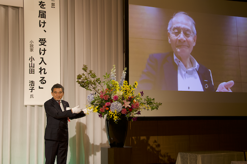السيد أوتشى (على اليسار) وهو يمنح السيد أكيرا يوشينو(على اليمين) درع لقب الأستاذ الفخرى