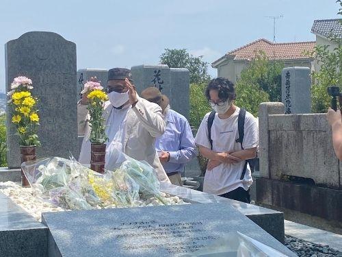 طالب أجنبى ودكتور كلاهما من ماليزيا يقيمان حفل تأبين أمام قبر السيد نيك يوسف