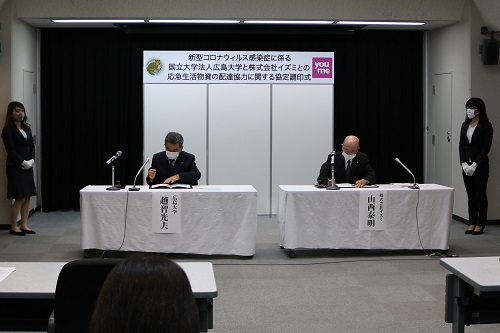 協定書に署名する越智学長と山西社長