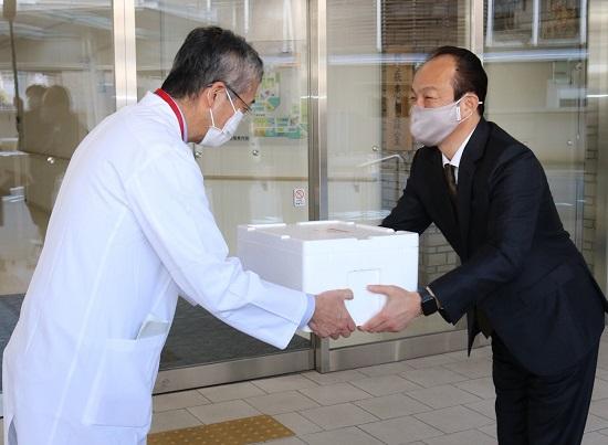 長野社長(右)から検査キットを受け取る木内病院長