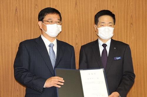 委嘱状を手にする相原副学長(右)