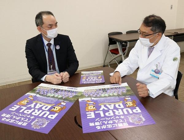 ポスターを見ながら話す松尾薬剤部長(左)と飯田てんかんセンター長