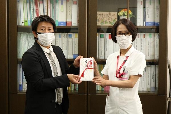 クーポンの目録を吉井副社長(左)から受け取った佐藤部長