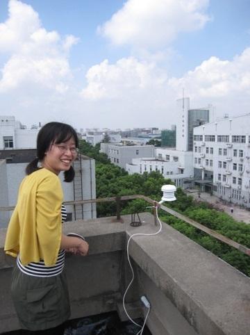 屋上で測定中の松尾さん画像