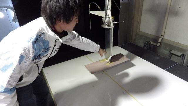 写真:実験施設にて説明している伊藤さん