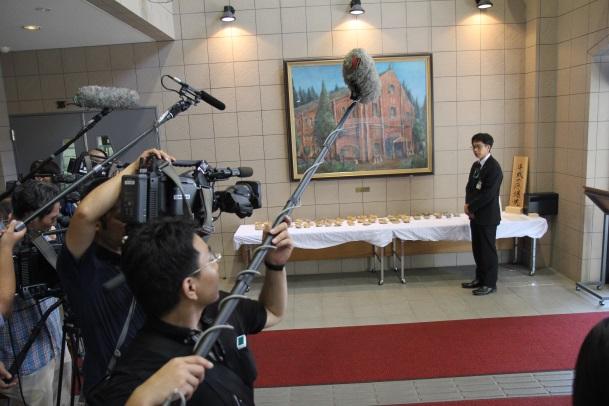 多くの報道陣を前に説明する嘉陽会長