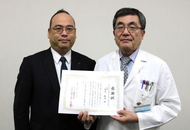 梶川社長(左)が平川病院長へ感謝状を贈呈
